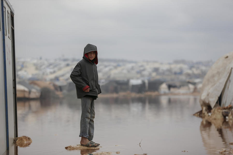On 19 January 2021, a child stands on a dry patch surrounded by floodwater in Kafr Losin Camp in northwest Syrian Arab Republic.
