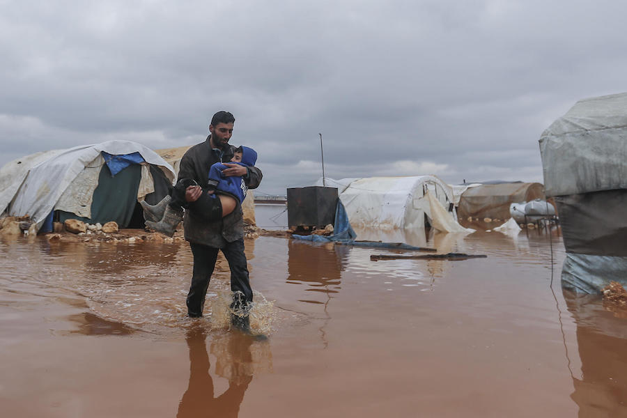 On 19 January 2021, Abu Qutaiba carries his 11-year-old son, Kamel, through a flooded area in Kafr Losin Camp in northwest Syrian Arab Republic.