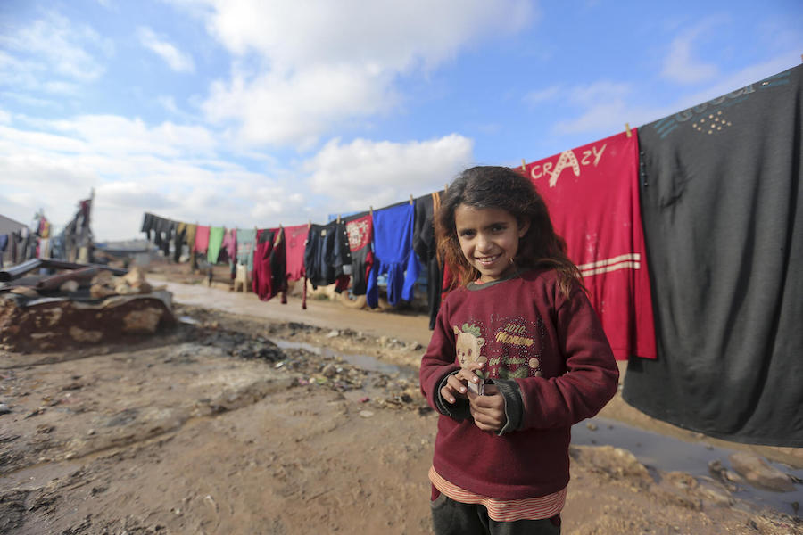 On 19 January 2021, a child stands in front of clothes hanging on a drying line in Kafr Losin Camp in northwest Syrian Arab Republic.