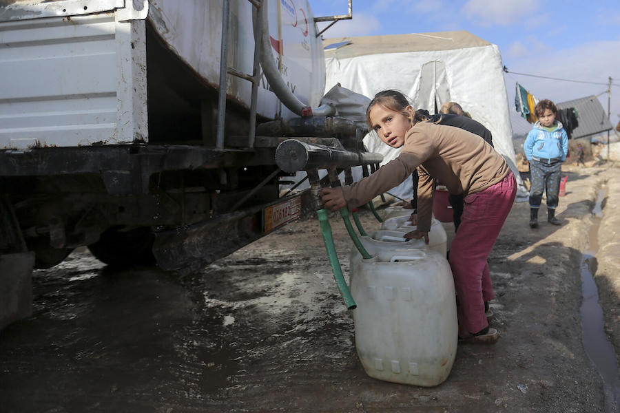 On 19 January 2021, a child collects water from a tanker truck in Kafr Losin Camp in northwest Syrian Arab Republic. UNICEF is working with partners to provide families with basic services.