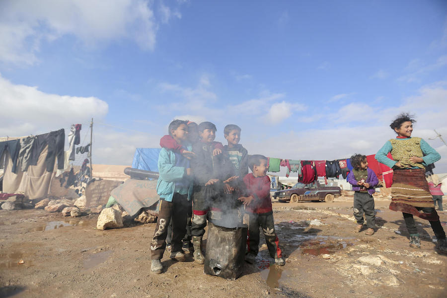 On 19 January 2021, children warm their hands by a fire in Kafr Losin Camp in northwest Syrian Arab Republic.
