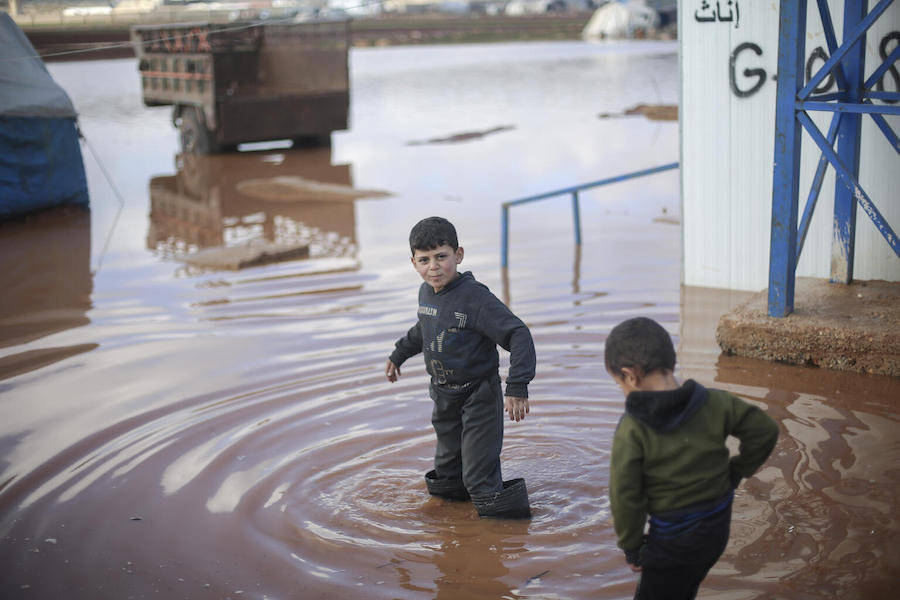 On 19 January 2021, children walk through a flooded area of Kafr Losin Camp in northwest Syrian Arab Republic.