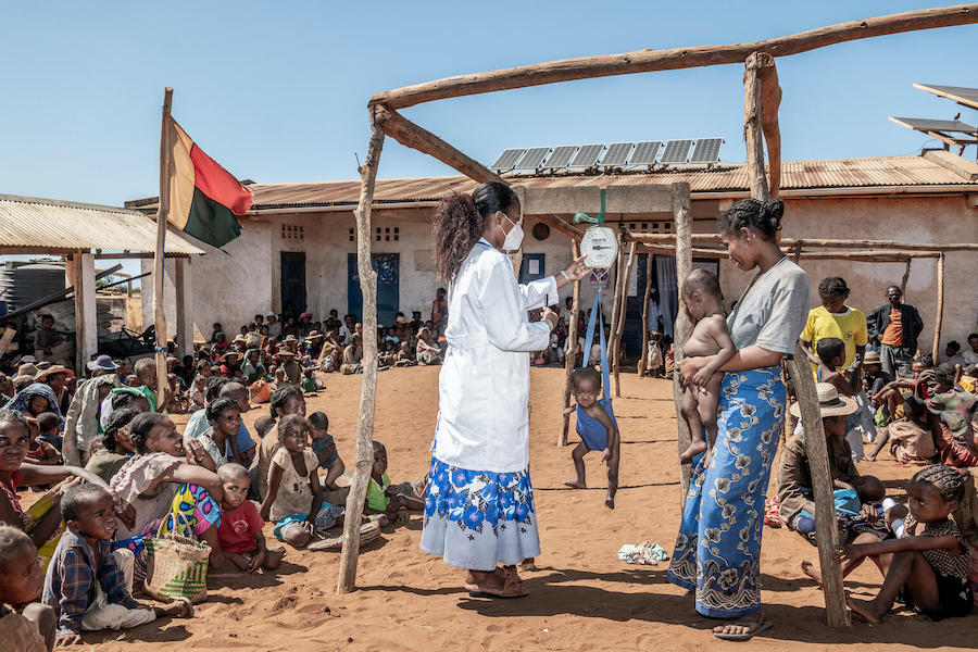Children are weighed by a health worker outside a facility in Maroalopoty where UNICEF supports malnutrition screenings and treatment, including the distribution of therapeutic food.