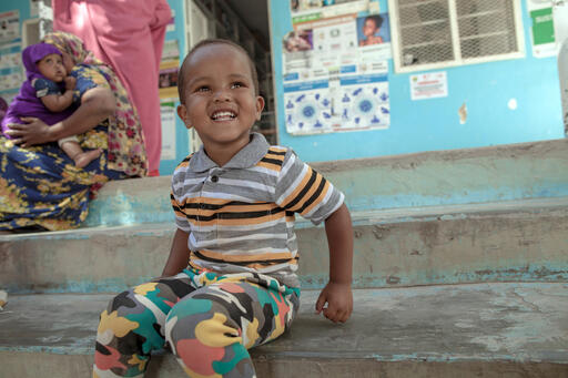Mohammed, 2, sits on the steps of a UNICEF-supported nutrition health center in Hargeisa, Somaliland, where both mothers and babies get the care they need to survive and thrive. Shop UNICEF Inspired Gifts.
