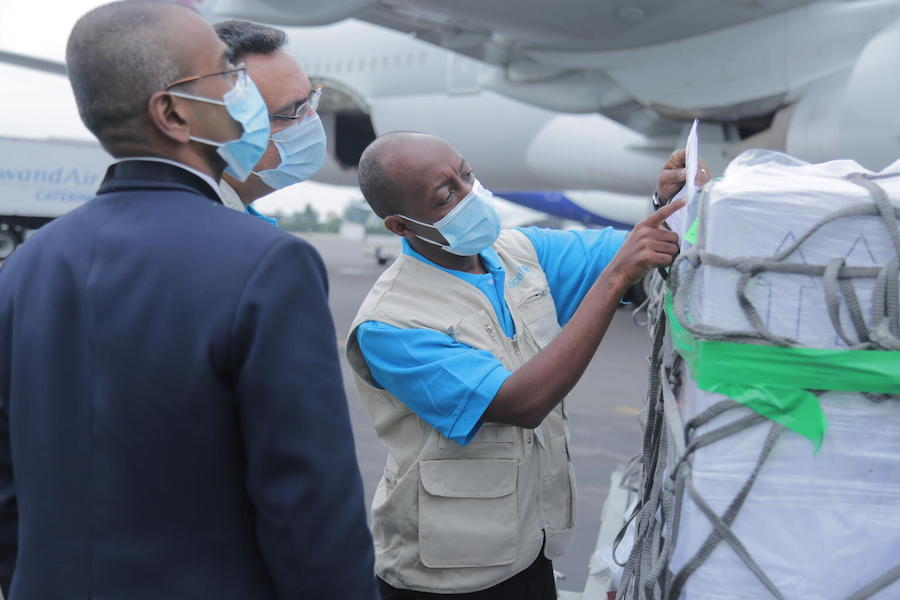 On March 3, 2021, UNICEF Supply Officer Mr. Denis Mupenzi, centre, inspects the cargo containing 240,000 doses of the COVID-19 vaccines for the COVAX Facility at Kigali International Airport in Rwanda.