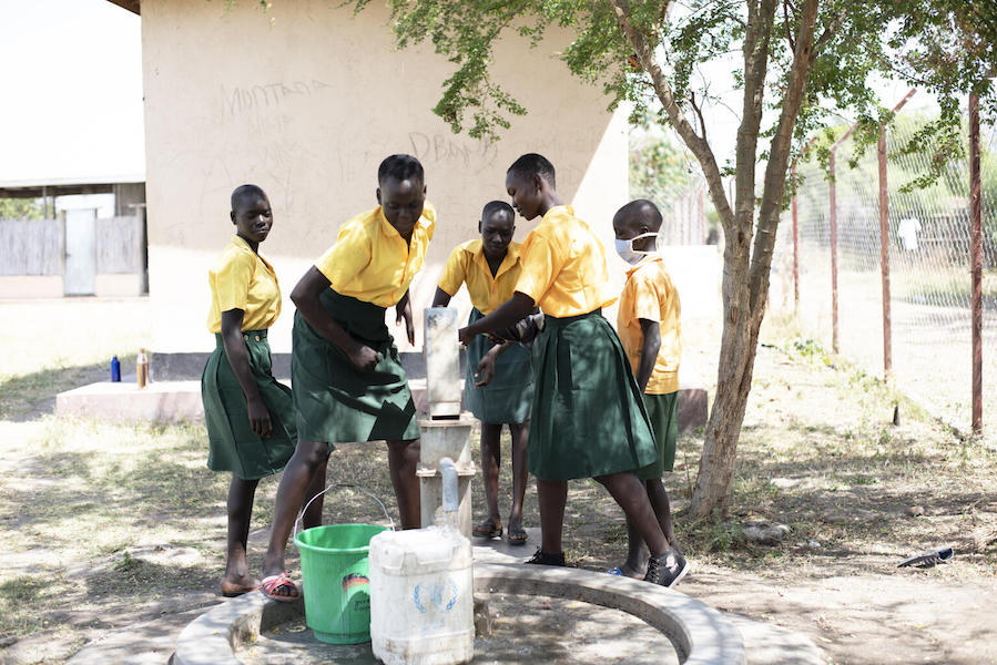 At Dumak Primary School in Torit, South Sudan on February 2, 2021, students fill buckets with safe water from a borehole rehabilitated by UNICEF and partners.