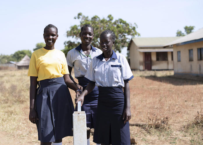 From left: Nite, 19, Elizabeth, 17, and Margaret, 17, stand beside a water borehole rehabilitated by UNICEF at Iluhum Primary School in Torit South Sudan.