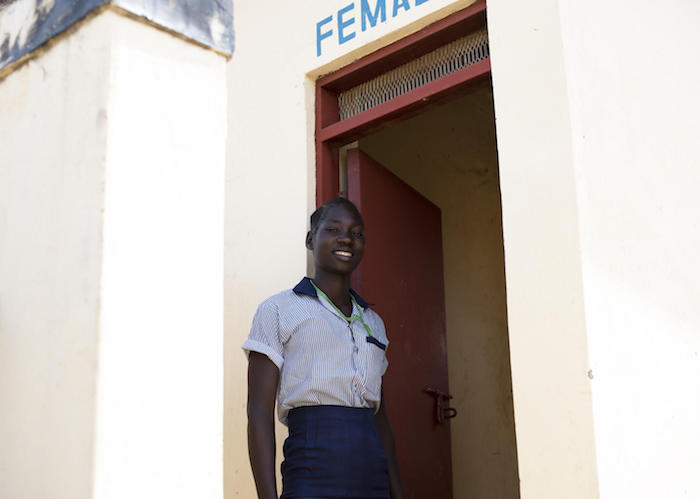 Elizabeth, 17, stands outside one of the latrines girls used to use before UNICEF rehabilitated their latrine block at Iluhum Primary School in Torit, South Sudan.