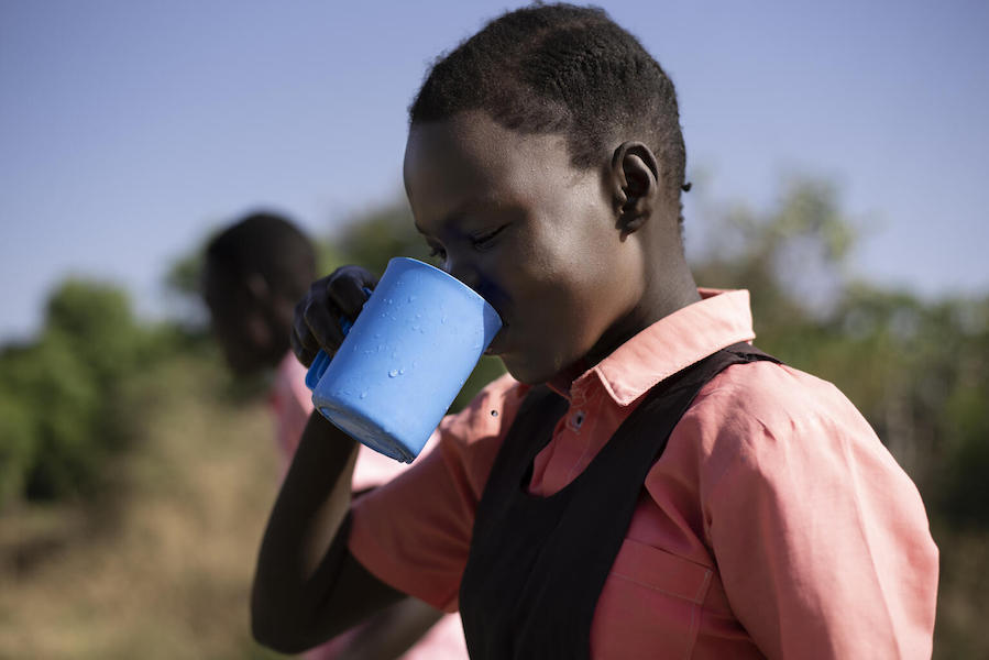 Keziah, 14, drinks water from the borehole at AIC Nursery and Primary School in Torit, South Sudan in February 2021.