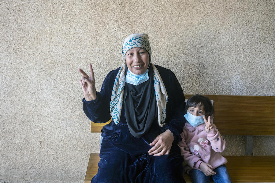 Syrian refugees Aesha, 62, and her granddaughter celebrate Aesha's COVID-19 vaccinate