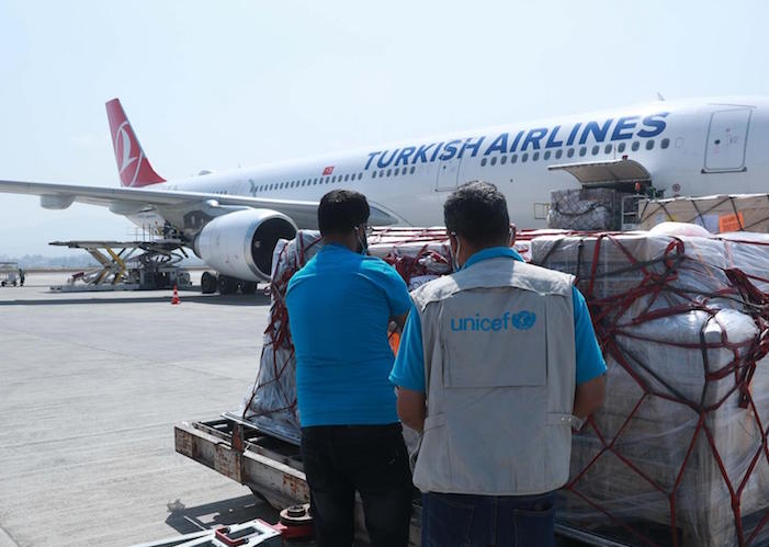 On March 11, 2021, UNICEF staff oversee the delivery of a COVAX shipment of syringes and vaccine safety boxes at the Tribhuvan International Airport in Kathmandu, Nepal.
