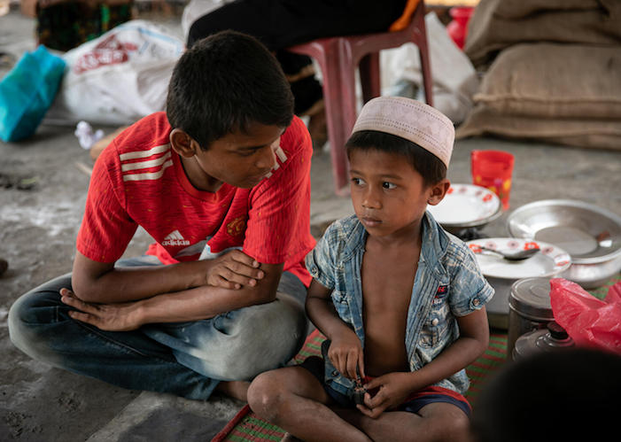 On March 24,2021, 18-year-old Mohammad Faisal comforts a younger Rohingya refugee after the fire that devastated the Balukhali area of the refugee camps in Cox's Bazar, Bangladesh.