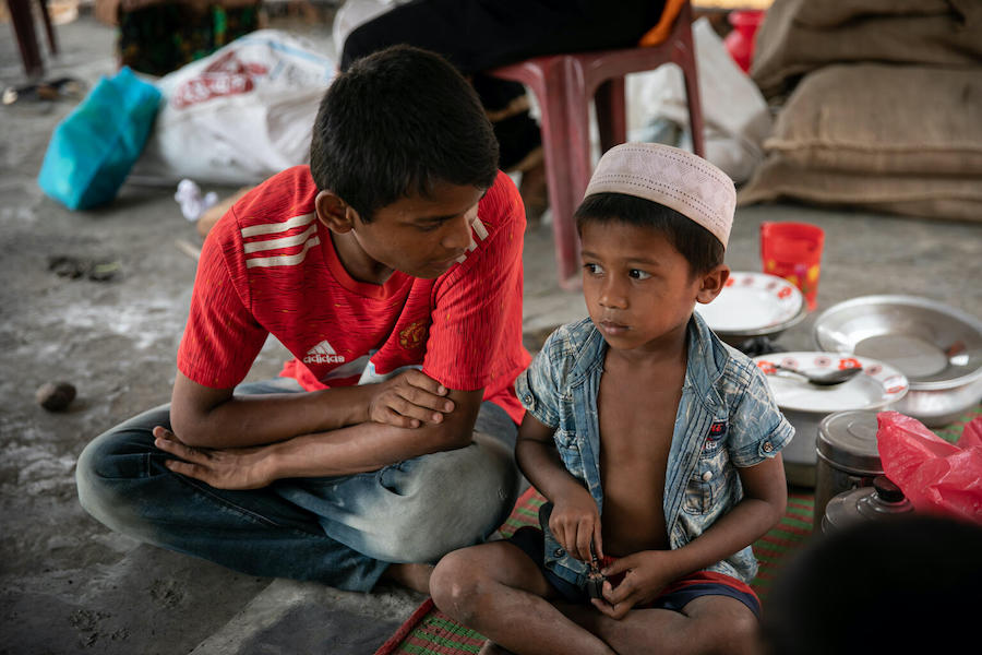 Mohammad Faisal, 18, comforts a younger Rohingya refugee while the child's family goes for help after their home was lost to the fire that devastated the Balukhali area of the Rohingya refugee camps in Cox's Bazar, Bangladesh.