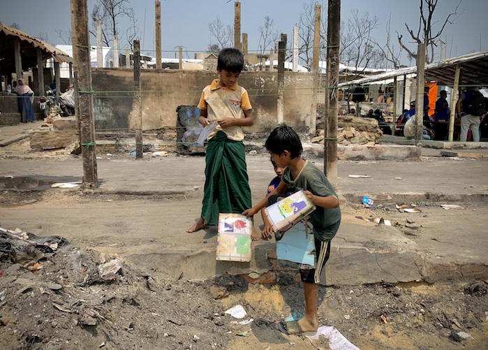 Some children visit their burned learning center to see if any reading materials could be salvaged after a fire destroyed a large part of Balukhali Rohingya refugee camps in Cox's Bazar on March 22, 2021.
