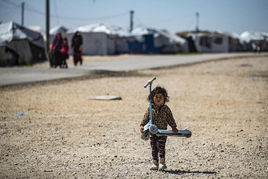 On March 18, 2021 in Syrian Arab Republic, a child carries a scooter while walking through al-Hol camp, which holds suspected relatives of Islamic State (IS) group fighters, in Hasakeh governorate of northeastern Syria.