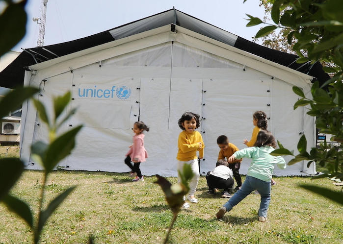 Children play inside and outside the new UNICEF High Performance Tents recently installed in Afghanistan to be used for community-based education programs.