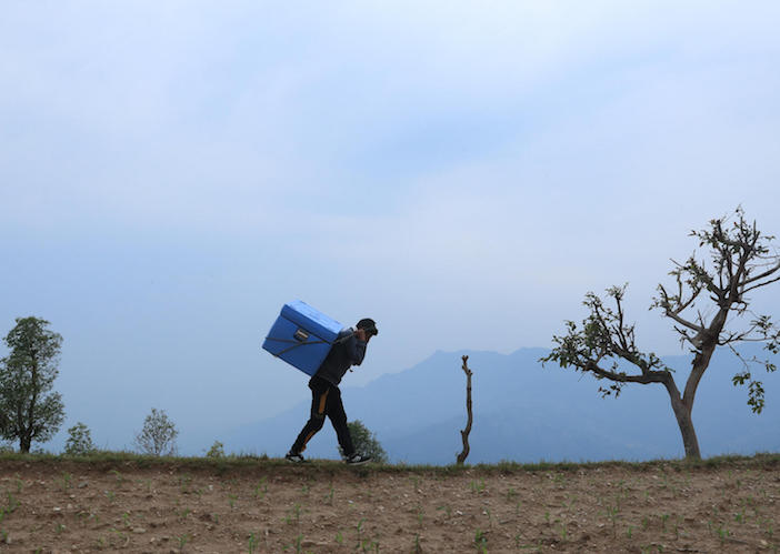 On April 21, 2021, Ram Dawadi, staff at the Bhachhek Health Post in Gorkha District in north-central Nepal, carries COVID-19 vaccines to the health facility, to be used to provide the second doses to health workers and frontliners in the area.