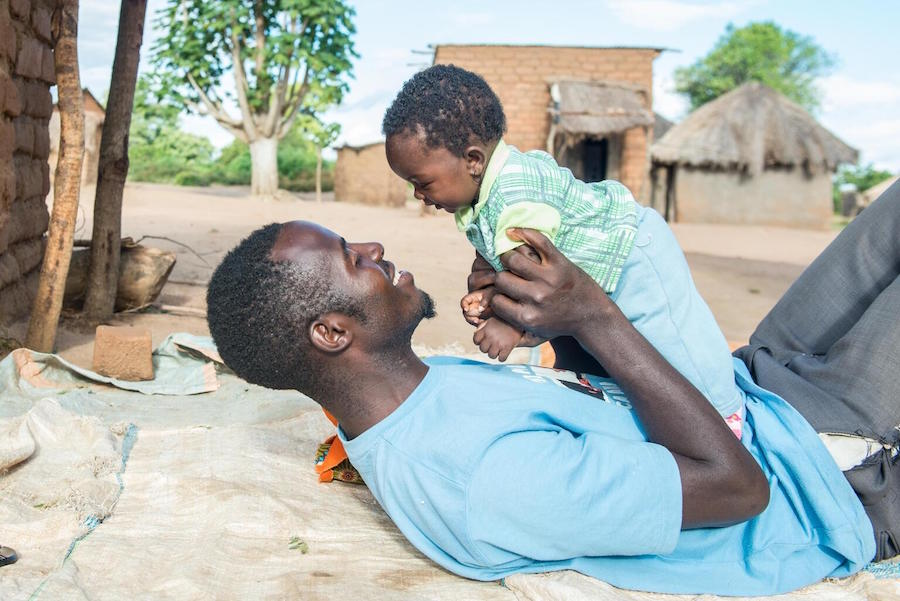 Lukas Phiri plays with his 4-month-old daughter Faith in Kholowa Village, Katete District in Zambia's Eastern Province.