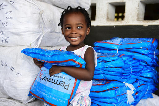 Marie, 2, receives mosquito nets with her father in Grand-Bassam, Côte d'Ivoire. A total of 19 million mosquito nets will be distributed to families to fight against malaria.