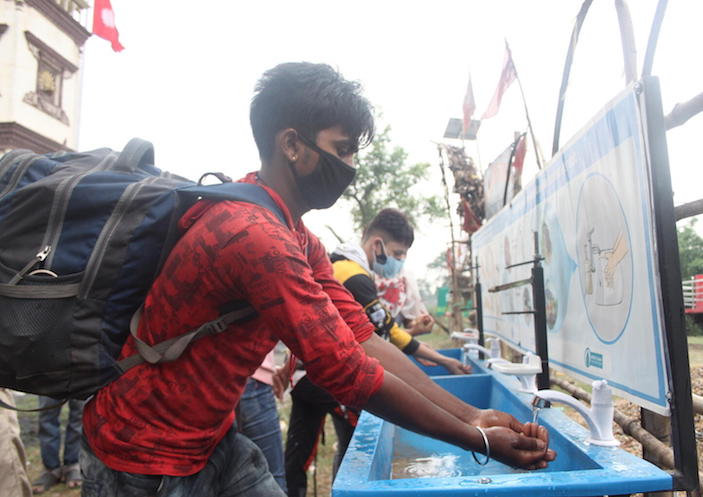 On May 5, 2021, travelers crossing from India to Nepal at the Birguni point of entry in southern Nepal's Parsa district wash their hands and receive temperature checks and antigen tests.