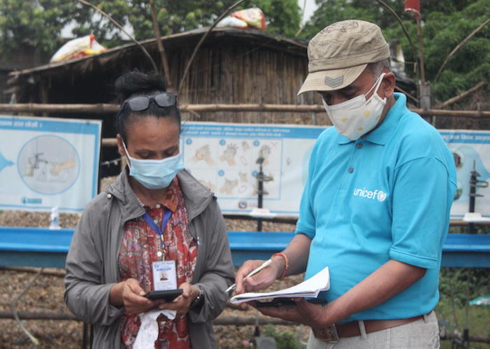 On May 5, 2021, a UNICEF staff member discusses COVID-19 health safety measures at the border crossing from India into Nepal at the Birgunj point of entry in Parsa District in southern Nepal.