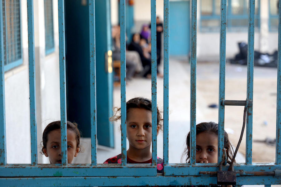 Three girls peeking outside a gate at one of 29 schools used as temporary shelter in Gaza in May 2021.