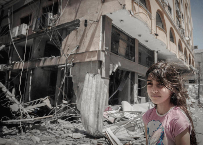 On May 17, 2021 in Gaza City, a Palestinian girl stands outside her family's damaged home while her parents hurry to remove some of their belongings.