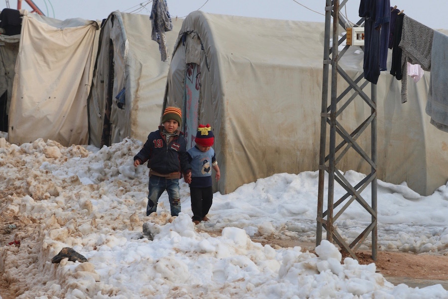 UNICEF Winter for Syrian Children: On 21 December 2016 at the Al-Nour IDP camp in rural Idlib, Syrian Arab Republic, two children walk in the snow and mud.