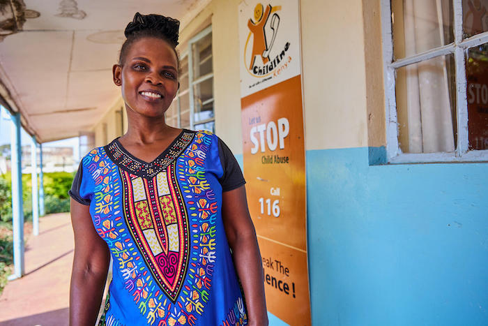 Helpline counsellor Barbra Sillingi stands outside the Childline Kenya call center where she works in Lower Kabete, on the outskirts of Nairobi.