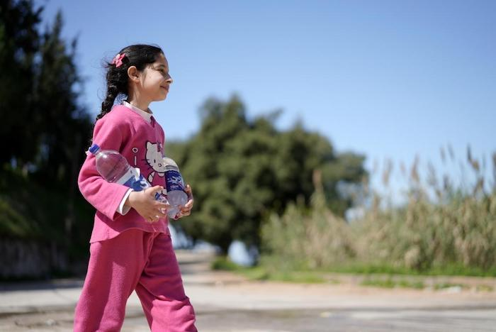 Syrine, 10, heads for home in Wadi El Jamous, Lebanon, with two newly-refilled bottles of water.