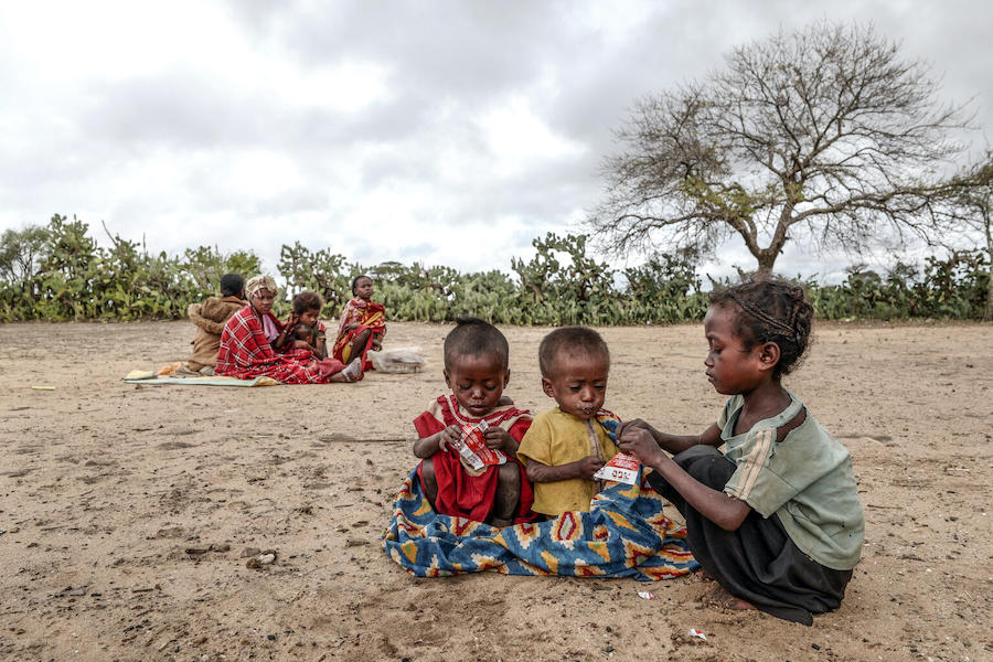 An older sibling gives therapeutic food to Samberahae, 3, and Fedraza, 2. The nutrient-rich peanut paste comes in packets that make it easy to distribute and use.