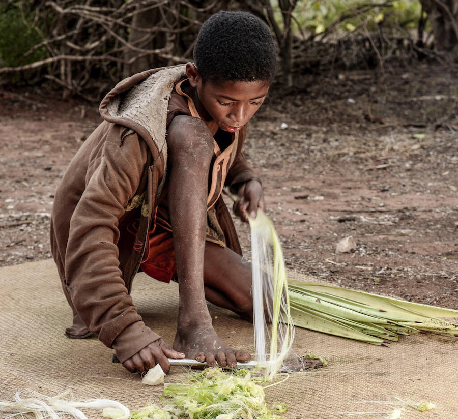 Laha, 14, uses a spear head to crush agave leaves with his foot and extract sisal fiber he can then sell at the market.