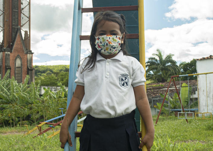 Paola, 6, and her classmates and teachers wear masks at their UNICEF-supported school in Venezuela's Táchira state.