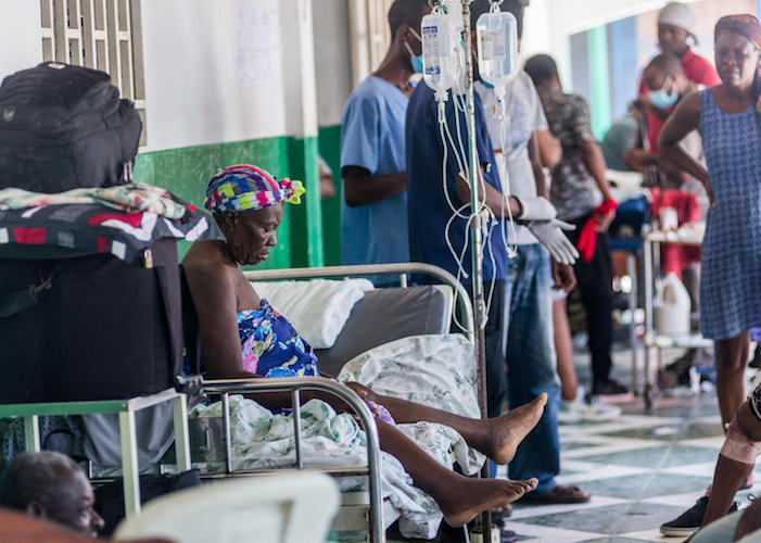 An injured woman rests on a bed at a hospital in Les Cayes on August 15, 2021, after a 7.2-magnitude earthquake struck Haiti's southwest peninsula.