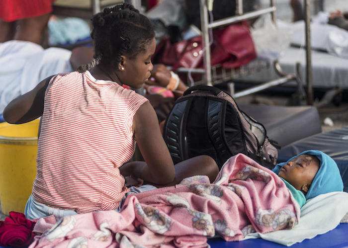 """A young mother looks on at her daughter, injured as a result of the earthquake at the hospital """"Communautaire de Référence"""" in Port-Salut, Haiti on August 16, 2021."""