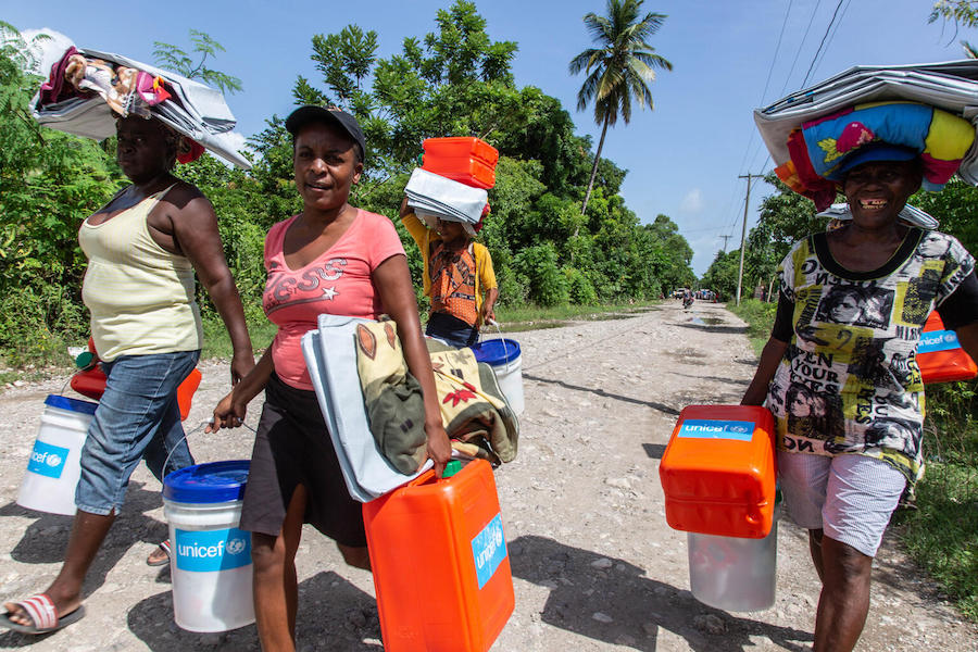 On August 18, 2121, just days after Haiti's powerful earthquake, people carry emergency supplies distributed by UNICEF in Valere, a village in Hait's Sud Department.