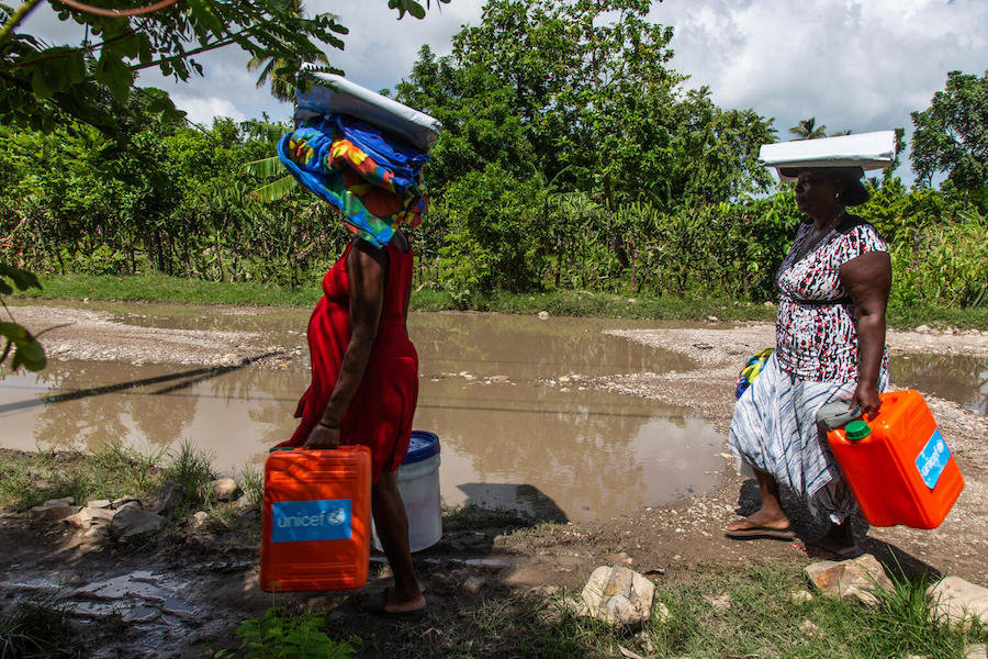 On August 18, 2021, Mera Marie Malia, a 38-year-old mother of five and seven months pregnant, left, and her neighbor, carry UNICEF-distributed supplies including tarpaulins and essential hygiene items, in Valere in Haiti's Sud Department.