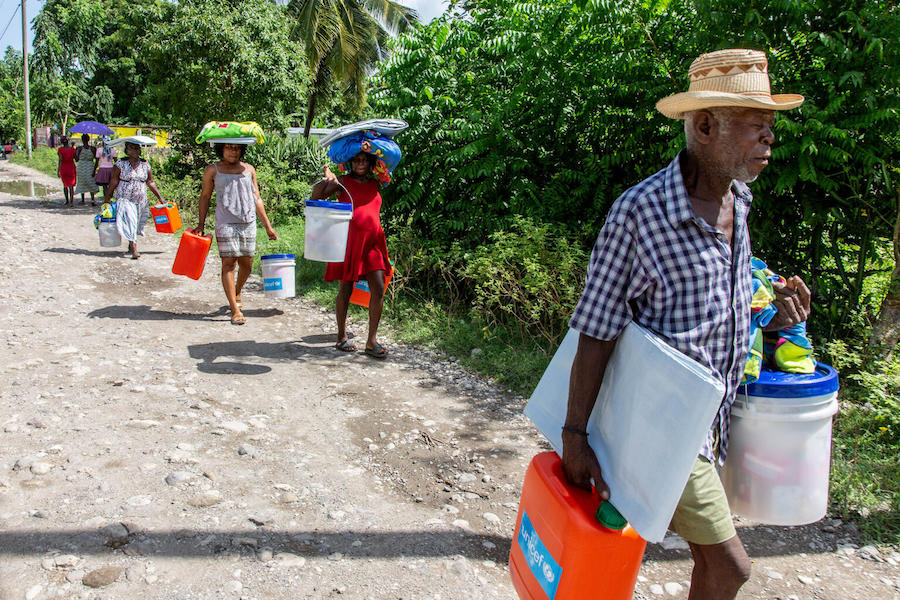 On  August 18, 2021, Mera Marie Malia, a 38-year-old mother of five (center, in red) and her neighbors receive an emergency kit containing tarpaulins and essential hygiene supplies in Valere, a village in Haiti's Sud Department.