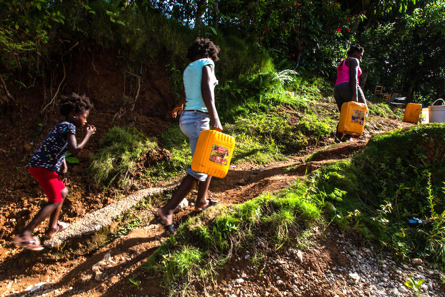 On August 18 2021, in Marceline, near Haiti's Camp Perrin district, people carry jerry cans of water from one of the four water stations supported by UNICEF in Les Cayes.