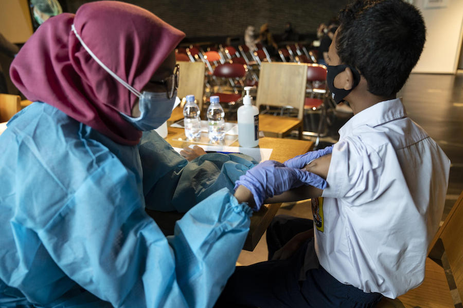 Fazil, 14, receives the COVID-19 vaccine at the Cilandak Town Square Mall in South Jakarta, Indonesia, on August 24, 2021.