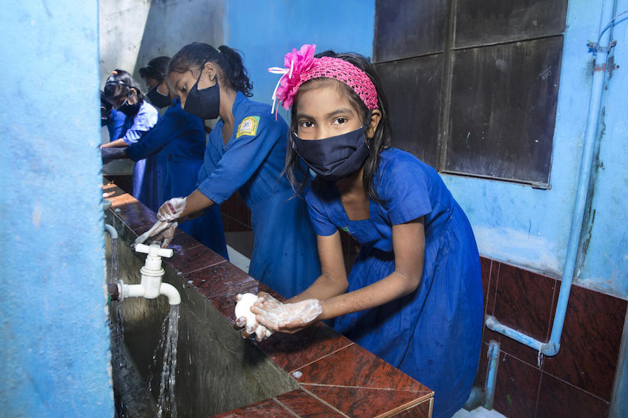 On September 12, 2021, children wash their hands properly before entering the classroom at Kalamarchara Government Primary School in Cox's Bazar, Bangladesh.