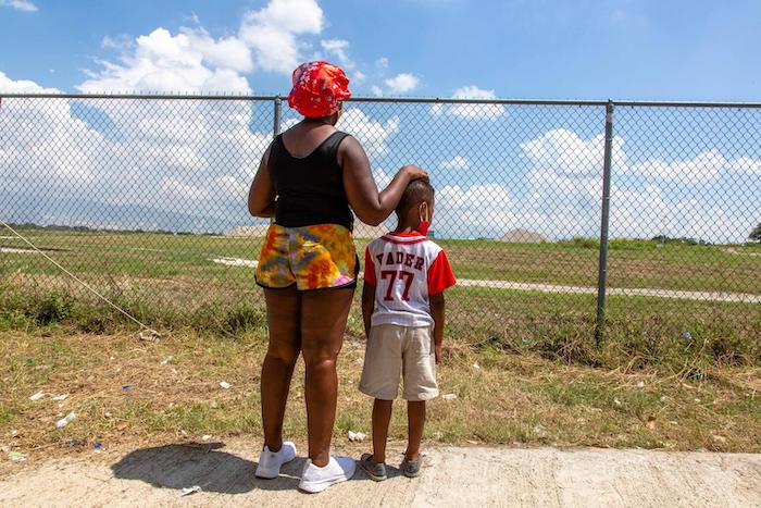 A mother and son look out over the airfield at Port-au-Prince airport after being returned from the U.S. border.