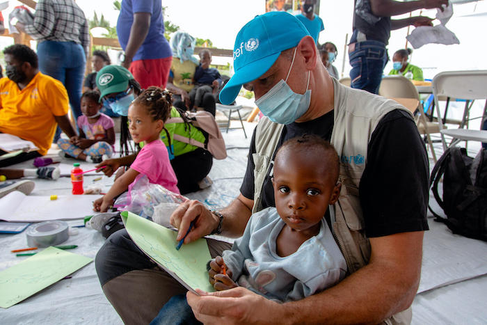 Laurent Duvilier, UNICEF Regional Chief of Communication in Latin America and the Caribbean, draws with 2-year-old Safmi upon her arrival from the U.S. border to Port-au-Prince Airport in Haiti.