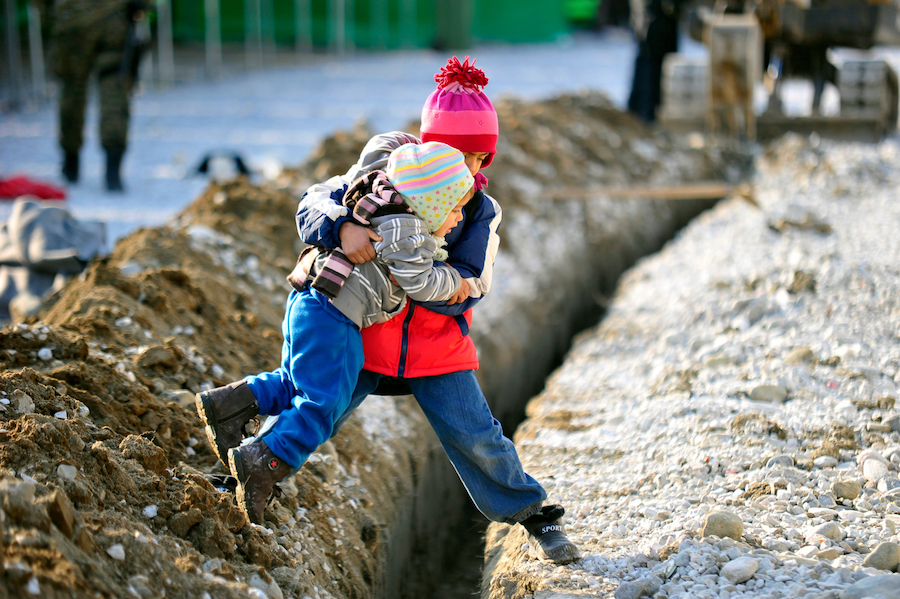 A boy helps his sister across a ditch at a refugee & migrant transit center in the fyrMacedonia. Child refugee crisis.