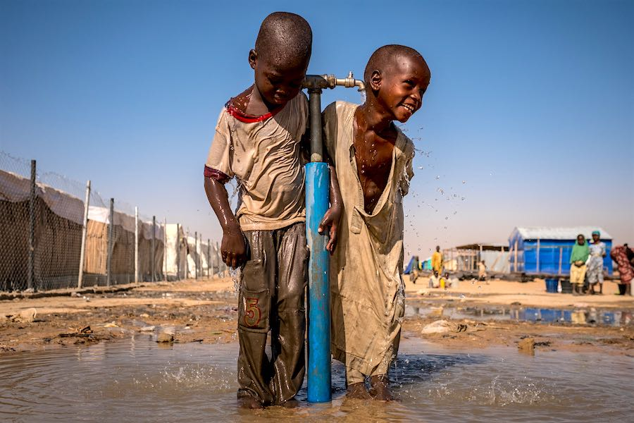 Children play under a water tap during a recess at a UNICEF supported primary school inside Bukasi Internally Displaced People's camp, in Maiduguri, Borno State, Nigeria