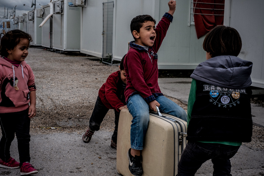 Children play with a suitcase they found in the garbage at the Skaramagas refugee camp, in the port area of northern Athens, Greece, in March 2017.