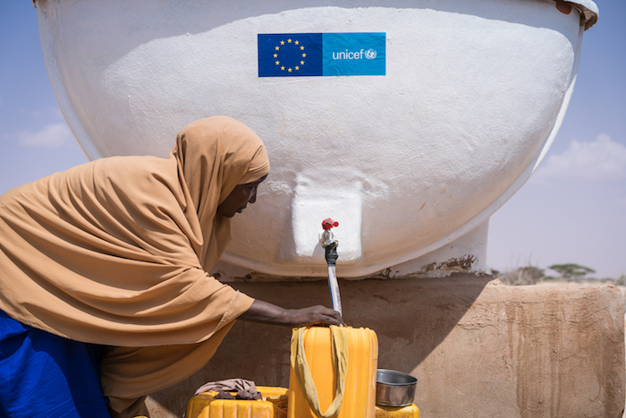 Drought forced this woman from her home. Now she fills containers with clean water in a camp in Galkayo, Somalia, for internally displaced people. Drought is worsening a situation that is especially grave for children, many of whom have stopped going to s