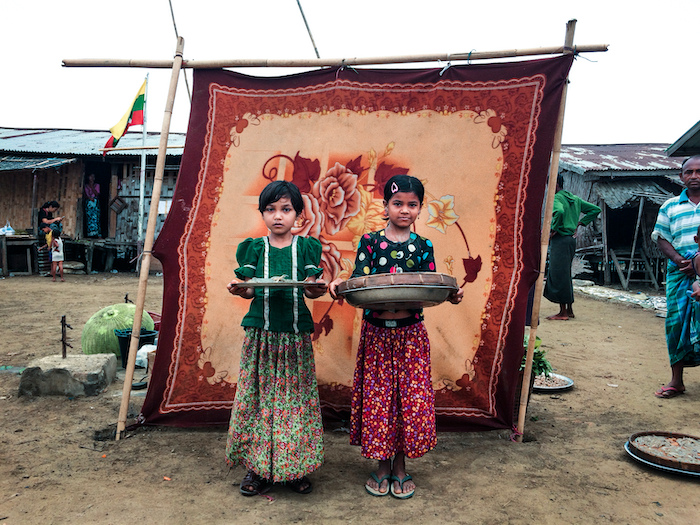 La La, 10, (left) and Noor Bi, 8, sell fish at the market in the Sin Tet Maw camp for families displaced by violence in Rakhine State, Myanmar.