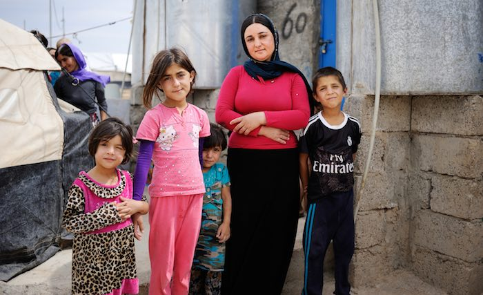 Besma stands with her children outside her tent in Bajet Kandala IDP Camp in Dohuk Governorate. She was shot by a sniper while fleeing her village in Sinjar in August 2014.