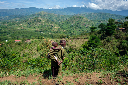 Jonathan Mbusa, 70, carries his 3-year-old granddaughter, Asinet, to a field in western Uganda, where they grow vegetables together. Asinet has been living with her grandparents since she was born. Jonathan creates a healthy, nurturing environment.